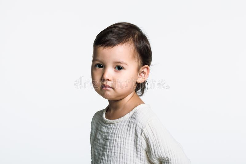 Studio portrait of a young girl staring at camera with sad eyes royalty free stock photography