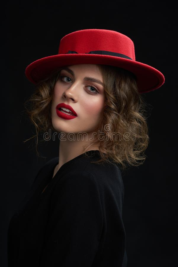 Studio portrait of young girl wearing red hat. royalty free stock photos