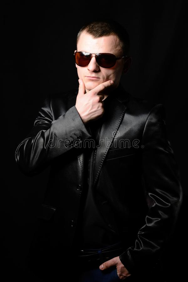 Studio portrait of a young guy with a short haircut in brown sunglasses stock image
