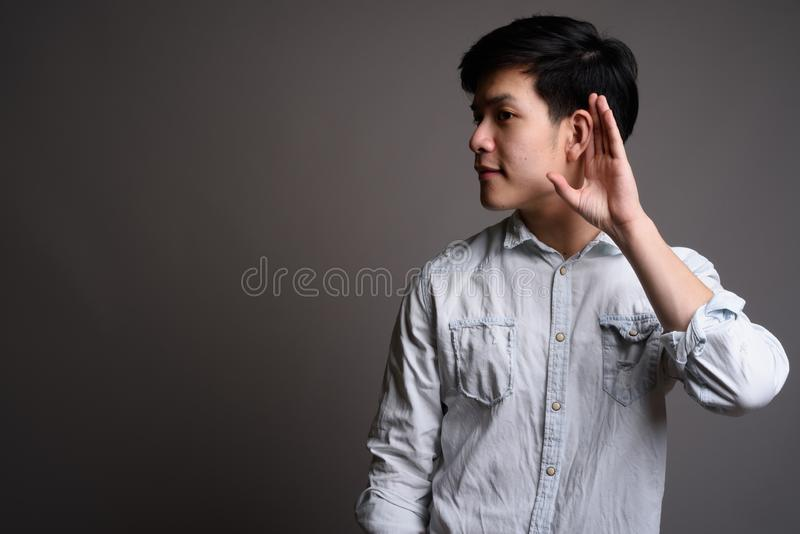 Studio portrait of young handsome Asian businessman klistening. Studio shot of young handsome Asian businessman wearing white shirt against gray background royalty free stock photography