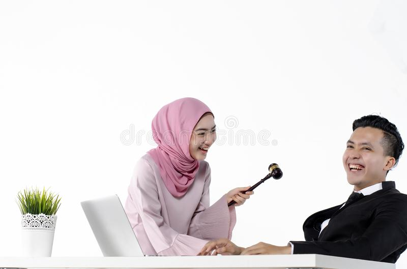 Young hijab muslimah joking with her officemate, funny and happy moment. Studio portrait of young hijab muslimah joking with her officemate, funny and happy royalty free stock images