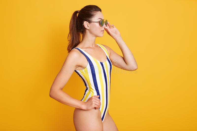 Studio portrait of young lady wearing striped swimmingsuit, beautiful girl dark hair and ponitail, posing isolated over yellow. Background, looking aside and royalty free stock photo