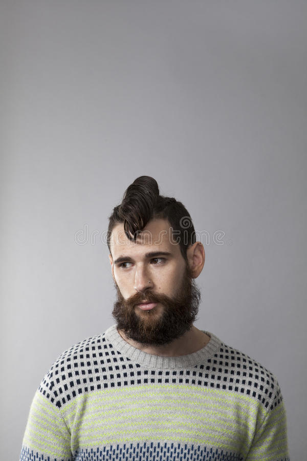 Studio portrait of young man with beard and tattoos stock photo