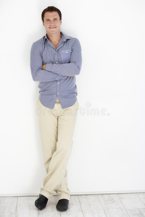 Studio Portrait Of Young Man Leaning Against White Background stock image