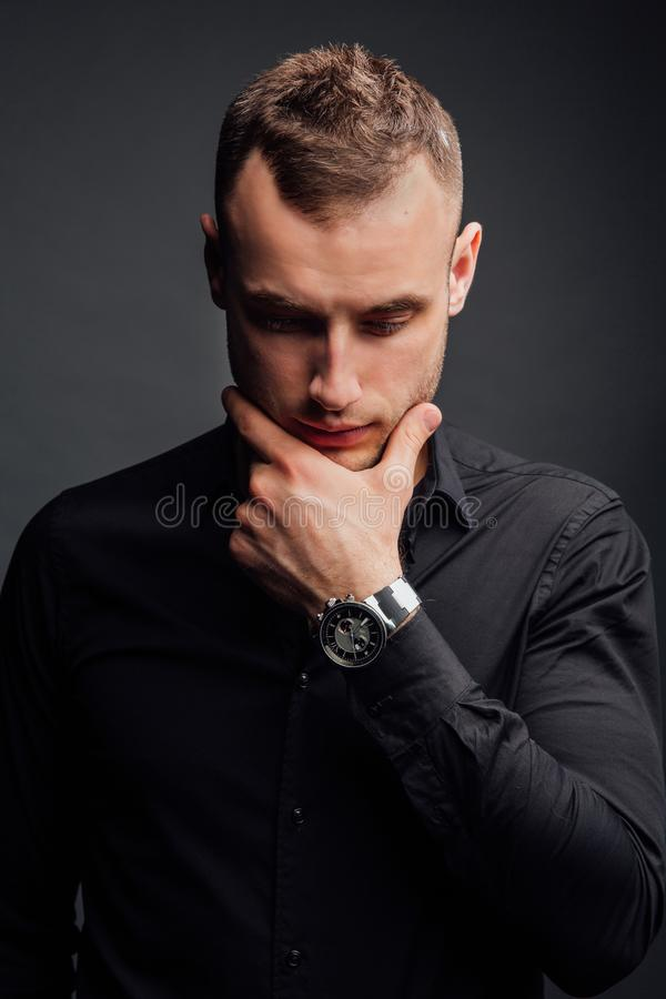 Studio portrait of young man in black shirt, holding hands in chin, looking down with humility. royalty free stock image