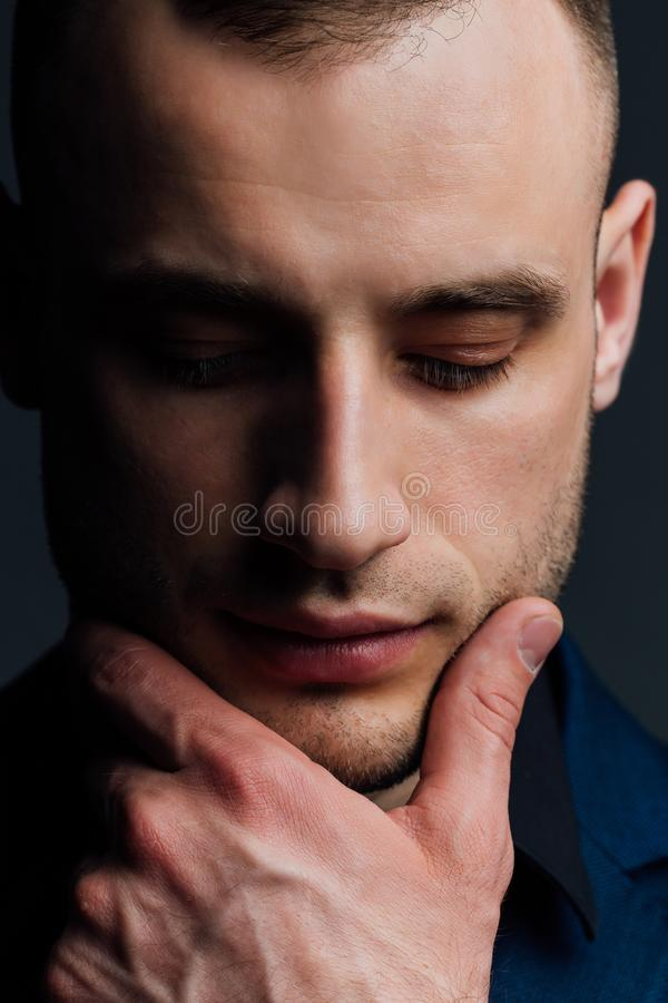 Studio portrait of young man in black shirt, holding hands in chin, looking down with humility. stock image