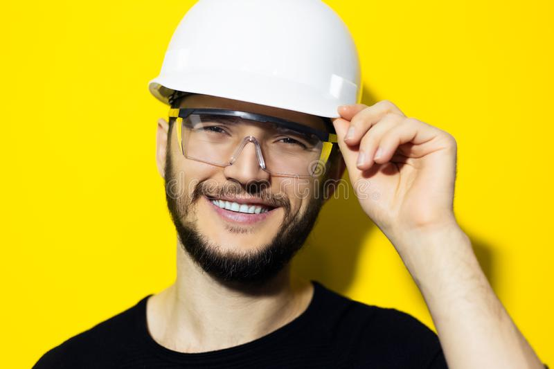 Studio portrait of young smiling man architect, builder engineer, wearing black sweater, touching his white construction safety he stock image