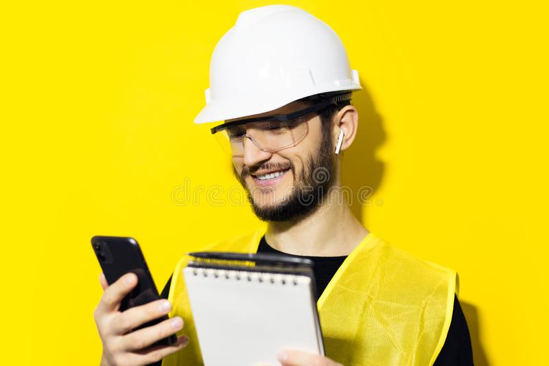 Studio portrait of young smiling man architect, builder engineer, wearing white construction safety helmet, glasses and jacket. Us. Ing smartphone and wireless royalty free stock photography