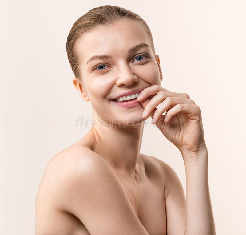Studio portrait of young, smiling woman. Healthcare, skincare concept on the peach color background royalty free stock photography
