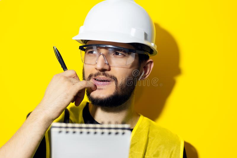 Studio portrait of young thinking man, builder engineer wearing safety helmet and glasses for construction on yellow background. Holding a pen and notebook stock image