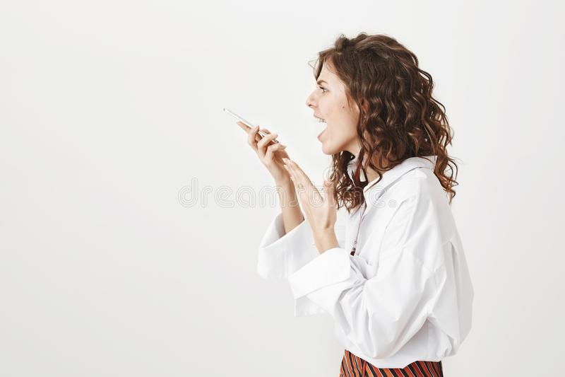 Studio portrait of young trendy woman standing in profile shouting at smartphone while holding gadget in hand, gesturing. With unpleasant and mad expression royalty free stock images