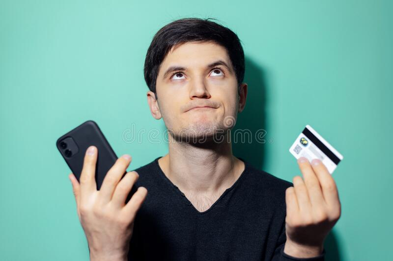 Studio portrait of young upset man looking up holding in hands smartphone and credit card on background of aqua menthe color. stock images