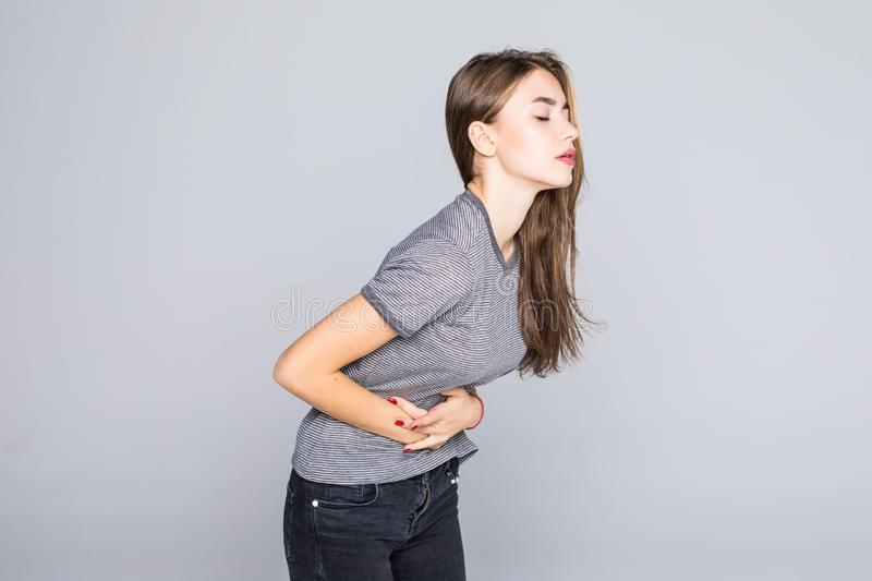 Portrait of young woman having a stomachache, menstruation pain or cramps, isolated on grey background. Studio portrait of young woman having a stomachache stock photos