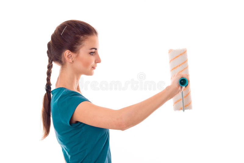 Studio profile portrait of young beautiful brunette girl in uniform makes renavation with paint roller in hands isolated royalty free stock image
