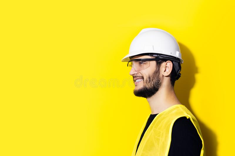 Studio profile portrait of young smiling man architect, builder engineer, wearing white construction safety helmet, glasses and ye. Llow jacket isolated on stock image