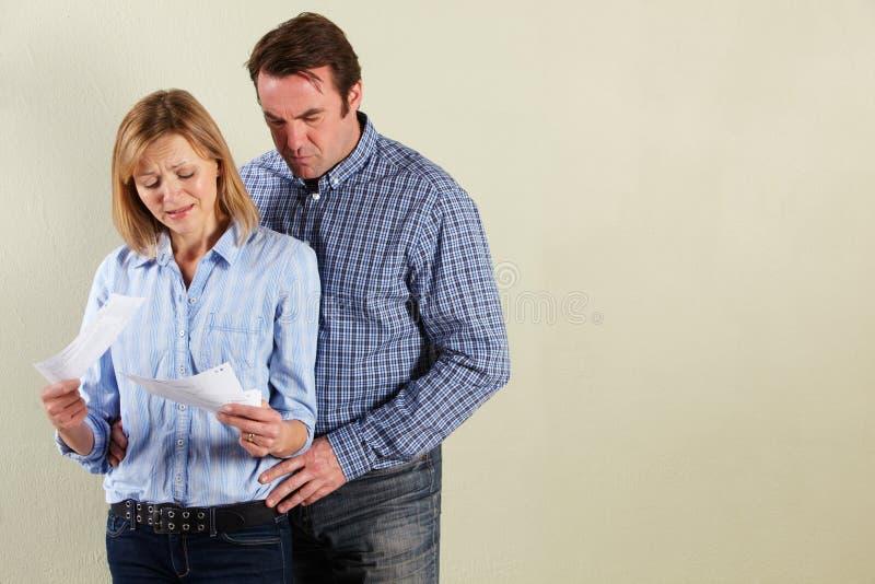Studio-Schuß der mittleren gealterten Paare, die Rechnungen betrachten stockfotografie