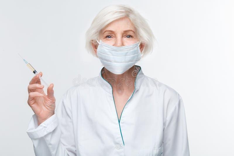Studio senior di medico della donna isolato sull'iniezione antinvecchiamento della parete della siringa bianca della tenuta fotografia stock