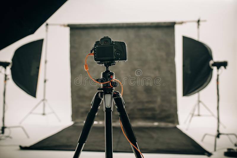 Digital camera mounted on a tripod in a photo studio. Studio setup with black background and studio flash lights with a DSLR camera on a tripod stock image