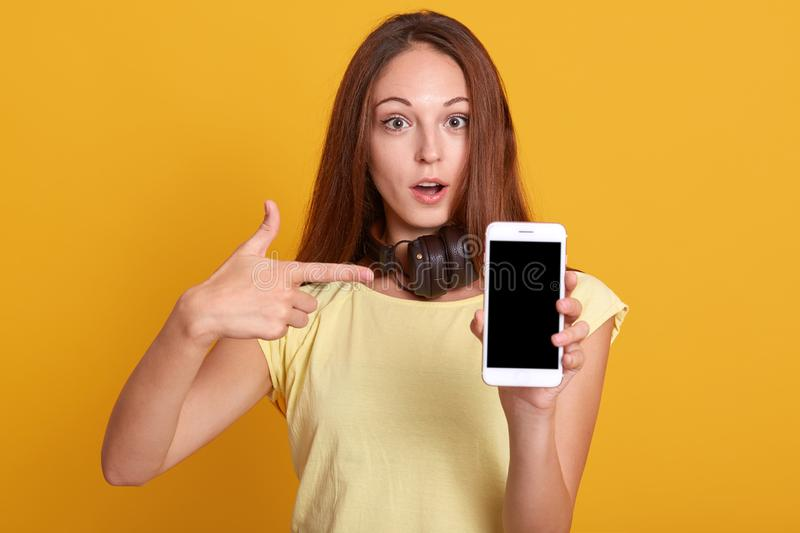 Studio sho of adorable woman showing phone with blank screen and pointing on it with her index finger, has astonished facial. Expression, keeps mouth opened royalty free stock photo