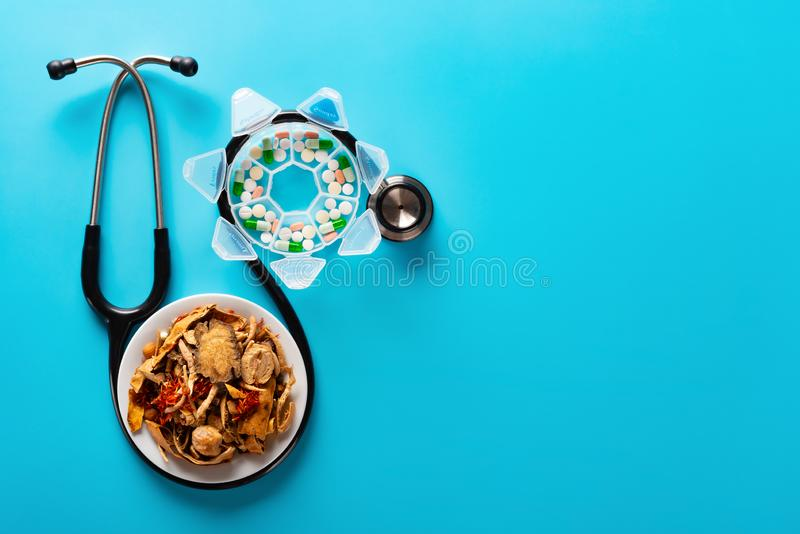 Studio shoot Chinese herb medicine and pills wrapped with a stethoscope on blue background. With copy space royalty free stock photography