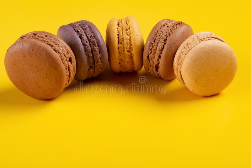 Studio shoot of colorful macaroons line up curved on yellow. Background stock photos