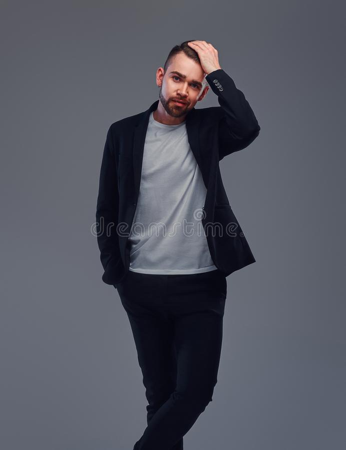 Studio shoot of trendy casual man in black suit and white t-shirt on grey background stock photography