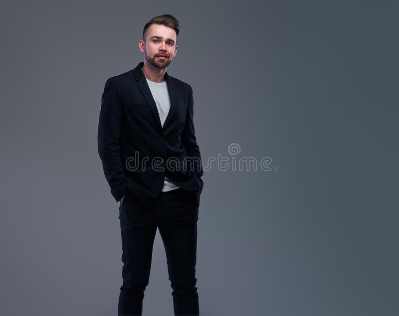 Studio shoot of trendy casual man in black suit and white t-shirt on grey background stock image