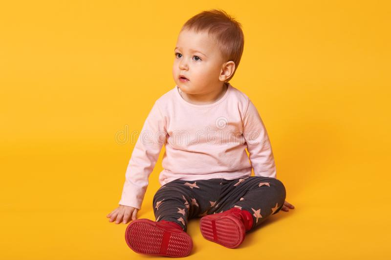 Studio shot of adorable little baby girl sitting on floor, isolated on yellow background, lovely baby portrait wearing casual stock images