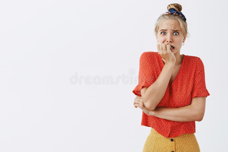 Studio shot of afraid nervous woman about to panic standing in vintage dotted blouse biting fingernails and staring. Concerned and worried at camera feeling royalty free stock photography