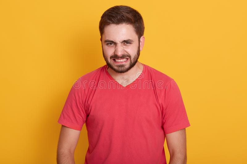 Studio shot of angry man wearing red casual t shirt, being displeased, keeps hands strained, unshaved guy with stylish hairdo. Twisted his face with anger royalty free stock photo