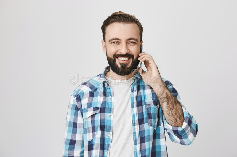 Studio shot of attractive cheerful european guy with beard and moustache, talking via smartphone and smiling broadly to royalty free stock photography