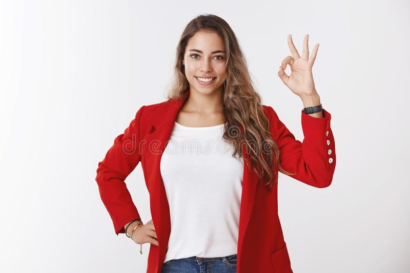 Studio shot attractive curly-haired 25s female lead team manager wearing red jacket approving project liking idea. Showing okay satisfactory gesture smiling royalty free stock image