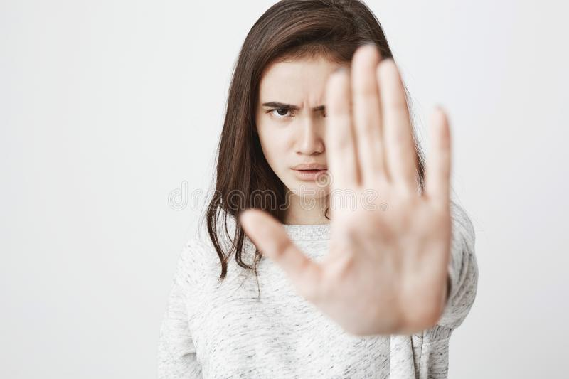 Studio shot of attractive european woman with concerned expression and frowned eyebrows, stretching hand in stop gesture. Isolated over white background. Girl stock images