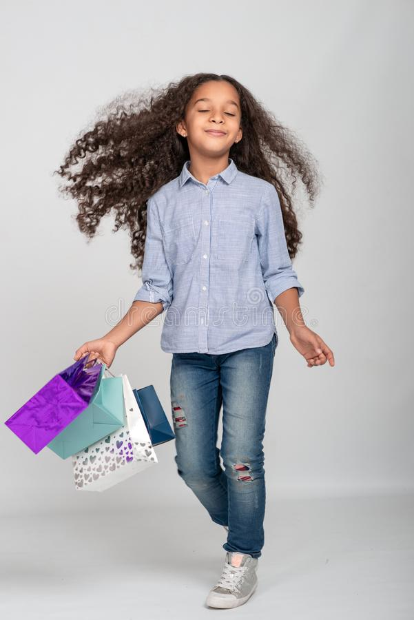 Studio shot of attractive little girl of mulatta with long frizzy. She has fun with paper bags from shopping, eyes closed from royalty free stock photo