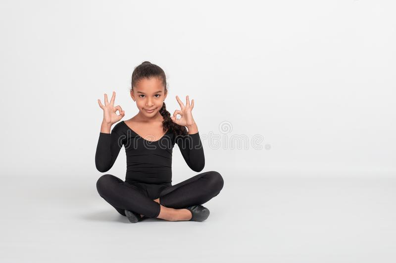 Studio shot of attractive little Mulatto girl gymnast siting on the floor with her legs crossed. She meditates gesturing with. Studio shot of attractive little stock photography