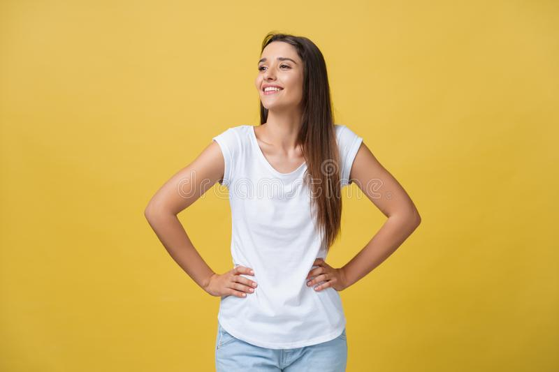 Studio shot of attractive self confident young female in great mood feeling happy, holding hands on her slender waist royalty free stock photography