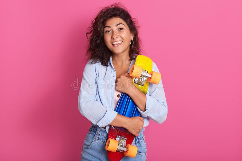 Studio shot of attractive woman with dark curly hair, looking directly at camera, embracing her skateboard, wears stylish clothes. Poses over pink background stock photography