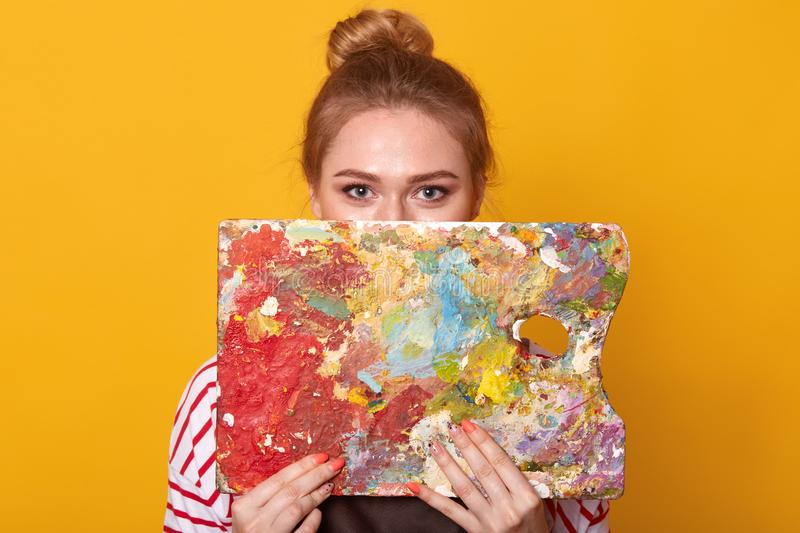 Studio shot of attractive young female artist holding and hiding behind color palette or her artwork, looking at camera, adorable stock images