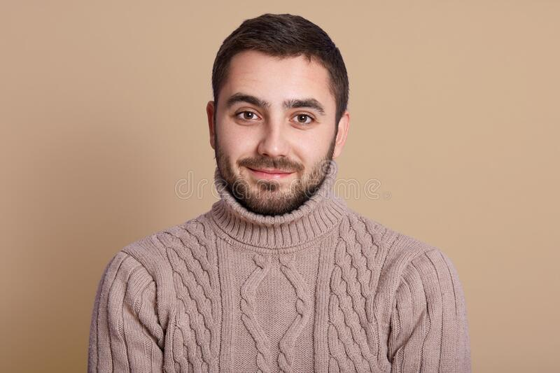 Studio shot of bearded man with pleasant appearance, looking directly at camera, posing isolated over beige background, handsome royalty free stock photos