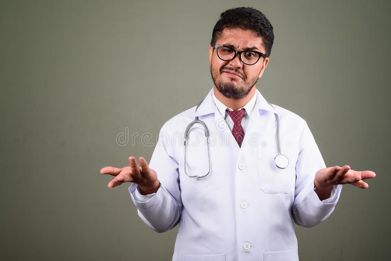 Bearded Persian man doctor against colored background. Studio shot of bearded Persian man doctor against colored background stock image