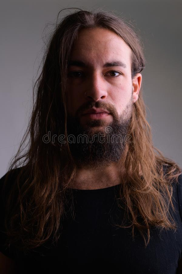 Face of young handsome bearded man with long hair stock images