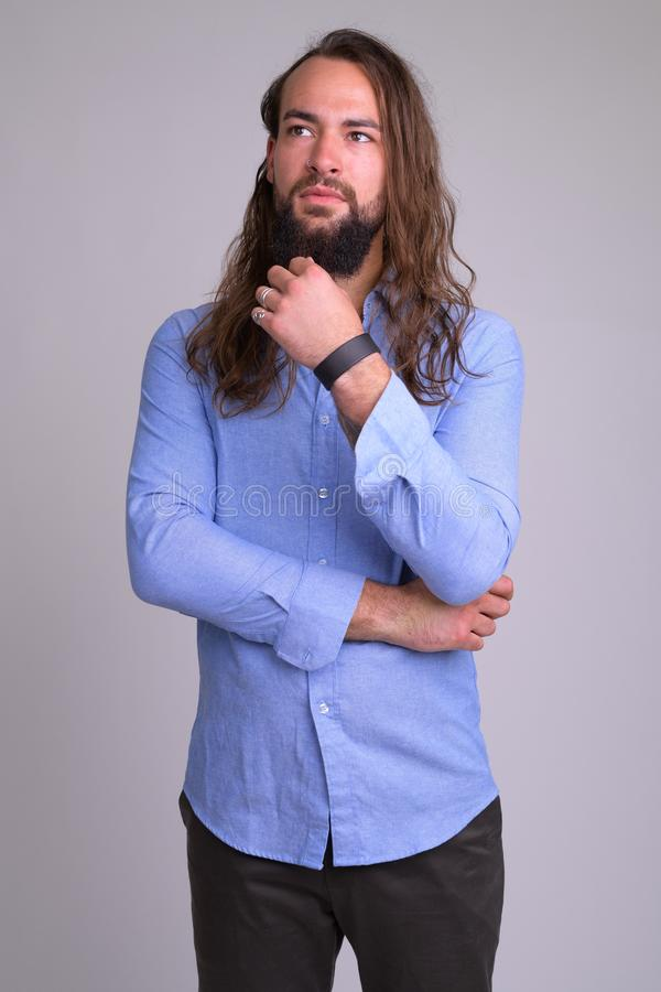 Portrait of young handsome bearded businessman thinking stock photos