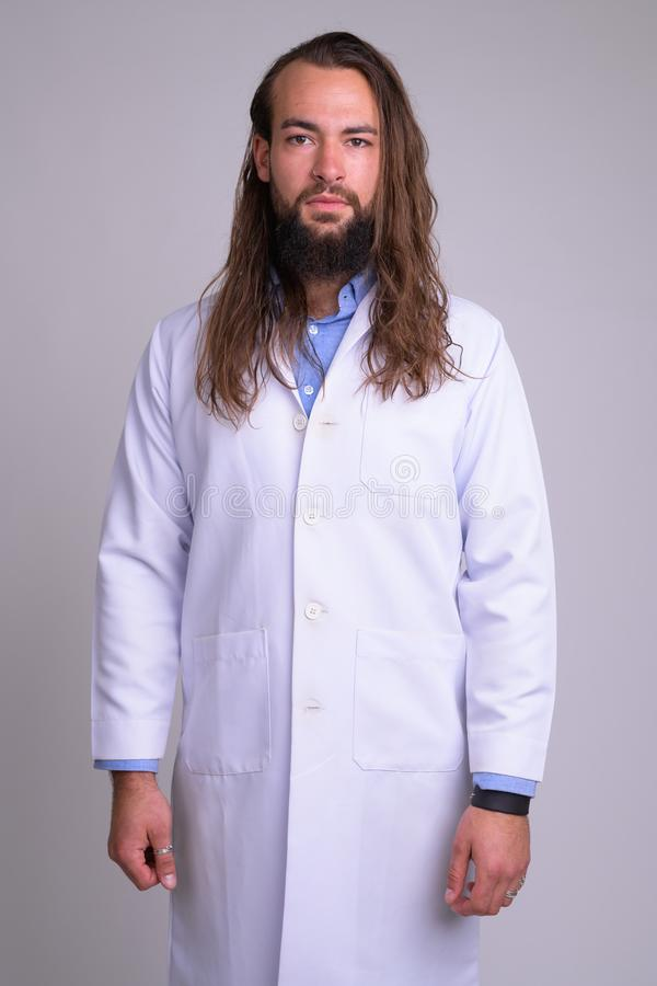Portrait of young handsome bearded man doctor stock photo