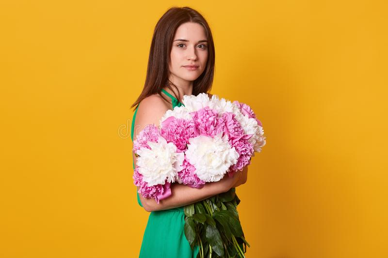 Studio shot of beautiful brunette female embracing big bouquet with pink and white peonies, stylish woman with flowers, has calm. Facial expression, posing stock images