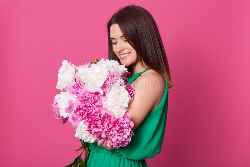 Studio shot of beautiful brunette girl embracing big bouquet with pink and white peonies, stylish charming lady posing against stock photography