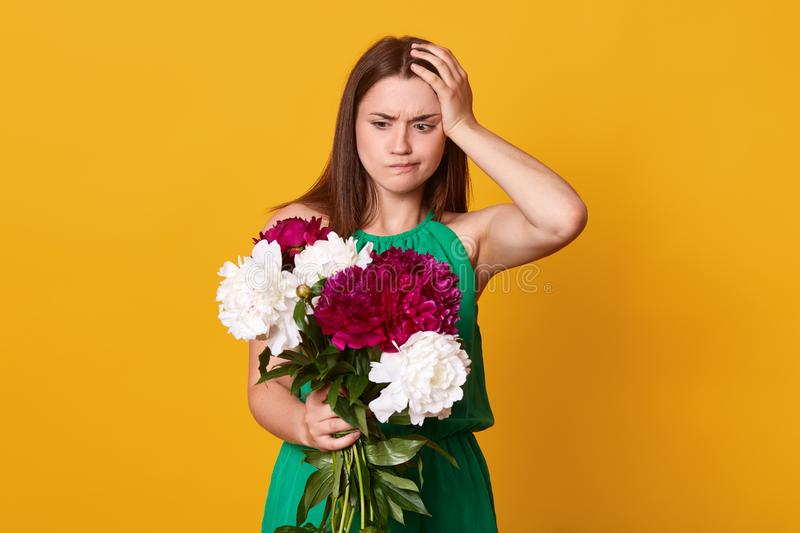 Studio shot of beautiful brunette girl holds big bouquet of burgundy peonies in hand, thoughtful woman with flowers keeps hand on. Head, poses against yellow stock images
