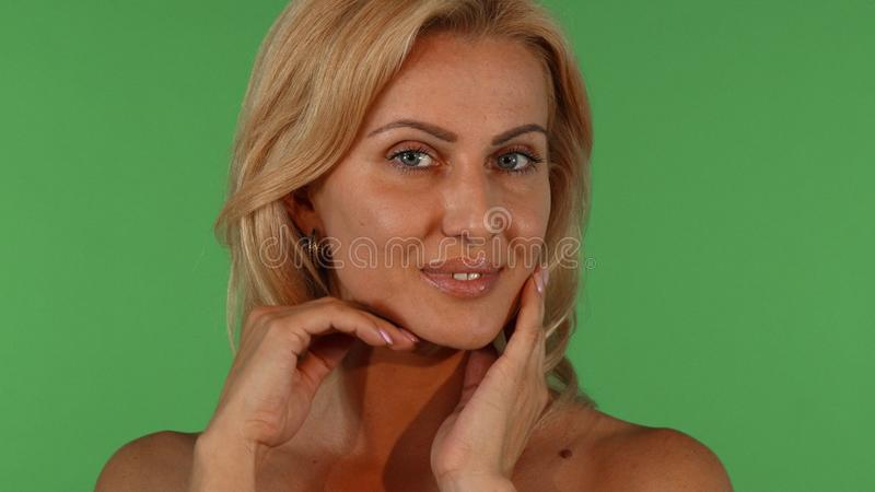 Gorgeous mature woman posing sensually on chromakey background royalty free stock photo