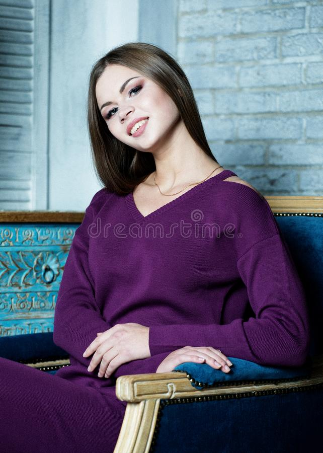 Studio shot of beautiful young woman wearing casual outfit sitting in a big comfortable chair and looking at camera stock photography
