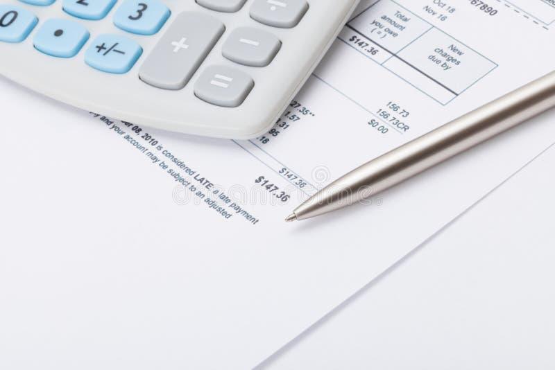 Studio Shot Of Calculator And Pen Over Some Receipt Stock Photo