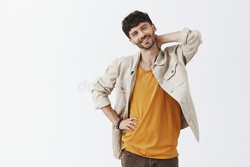 Studio shot of carefree handsome and confident caucasian guy with beard tilting head touching neck stretching back after stock image